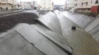 شاهد بالفيديو والصور.. انهيار الحواجز الأسمنتية لوادي أبها تحت مفيض السد