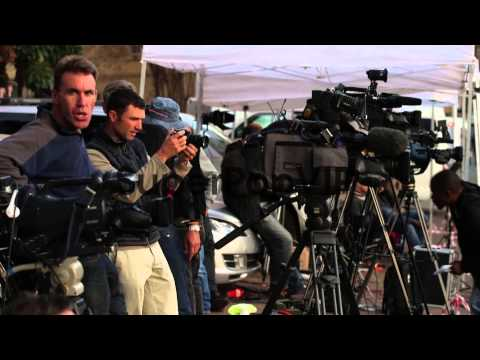 Mid shot, Television journalists set up across the road f...