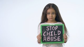 "Indian girl showing a slate with ""stop child abuse"" text isolated over white background"