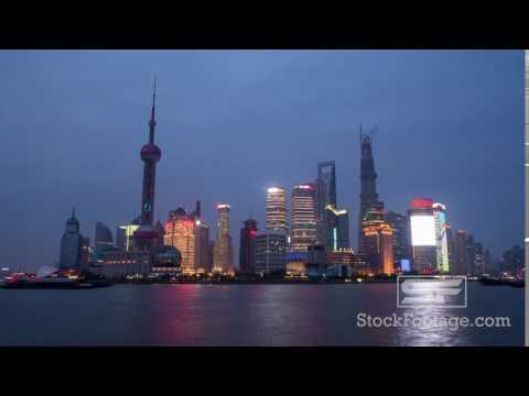 Time lapse of boats floating by with towers in the back in Shanghai China, at sunset.