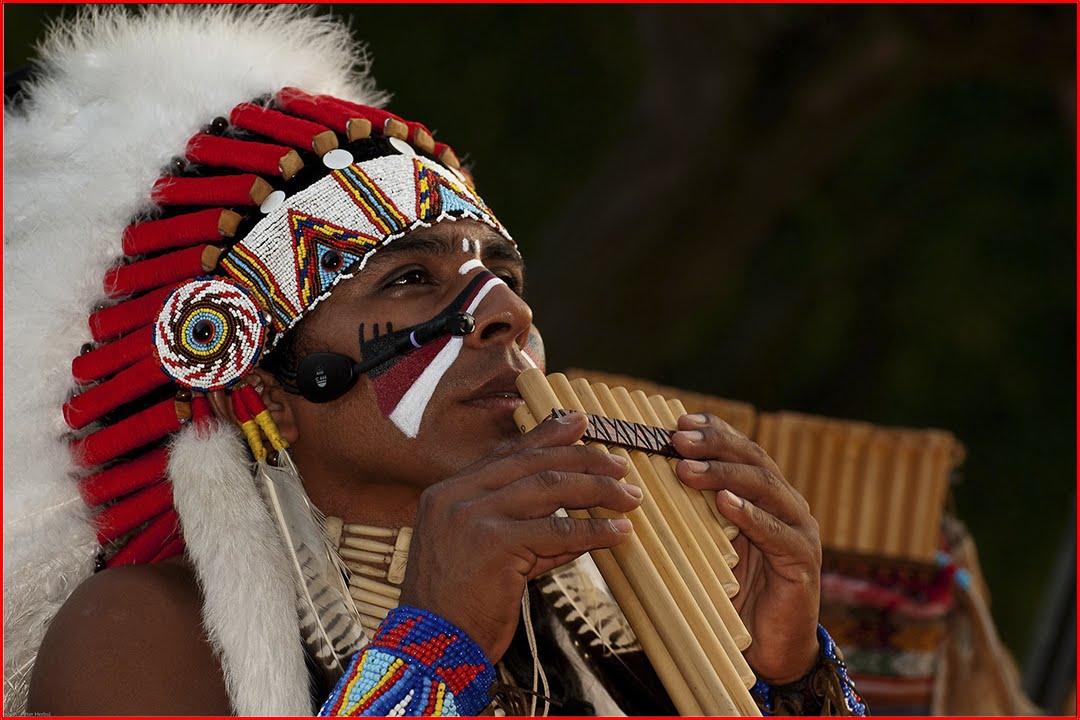 Мужчина из индейского племени играет кавер на