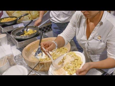 Dumplings Drowned in Melted Parmesan Cheese Wheel. Italy Street Food