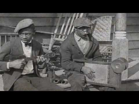 Street musicians Carl Scott and Eddie Thomas playing ukulele, kazoo, washboard, and a coffee pot.
