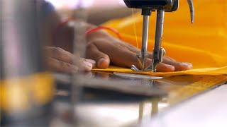 Hands of an Indian female tailor working on a sewing machine - sewing process