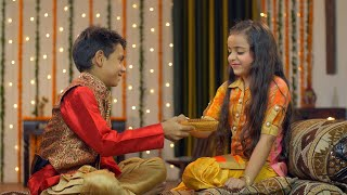 Smiling young Indian kids performing Raksha Bandhan / Bhai Dooj traditions - festive feels