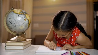 Cute little preschooler making drawing and coloring on study table posing isolated - study concept