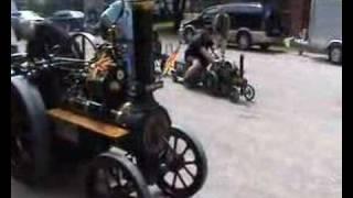 Ein Pflug - Lokomobil zieht mit dem Pflugseil ein Bobbycar