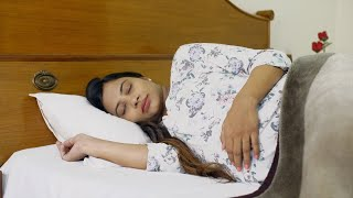 Beautiful pregnant woman touching her belly while sleeping in bed - lifestyle concept