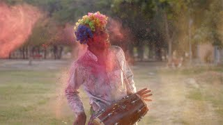 Funny Indian guy wearing a colorful hair wig celebrating the Indian Holi festival