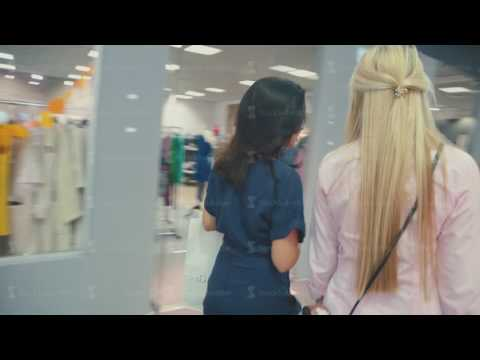 Two friends in a shopping centre. Young woman walking in the mall