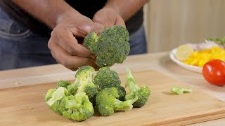 Closeup shot of a man preparing / breaking raw broccoli for cooking