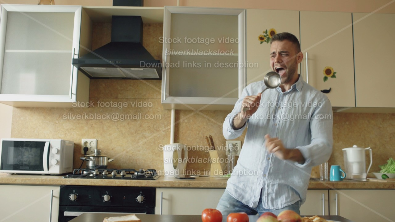 Attractive Young Funny Man Dancing And Singing With Ladle While Cooking In  The Kitchen At Home