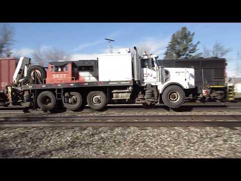 CN Highway-Rail Truck pulling Grand Trunk Western flat cars in Pavilion, MI past CN local train