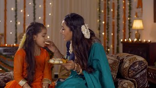 Indian mother and daughter in tradtional dress during the festival celebration - Mother feeding sweets to her daughter