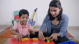 Shot of a young Indian mother and son playing with building blocks - Spending time at home during summer vacation
