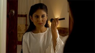 Pretty young Indian woman applying makeup on her cheek with a brush - Applying face powder