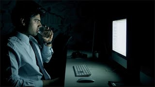 A tired IT professional typing on keyboard in front of computer at night and drinking water from a glass