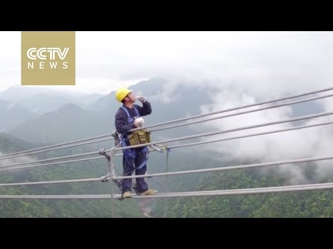 Men on wire: Power workers walk in the clouds to repair line