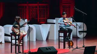 Giri and Uma are seen on stage at TedX Nashville at teh Schermerhorn Symphony Center. They are dwarfed by the huge screen on which videos are show. Each of them sits on a stool at a microphone as they talk and perform. (thumbnail)