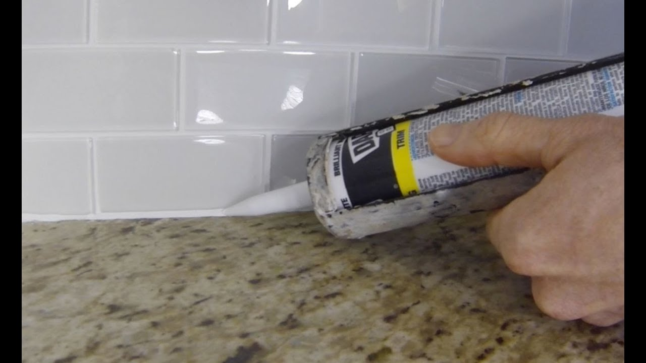 How to install caulk on a kitchen tile backsplash youtube How to put tile on wall in the kitchen
