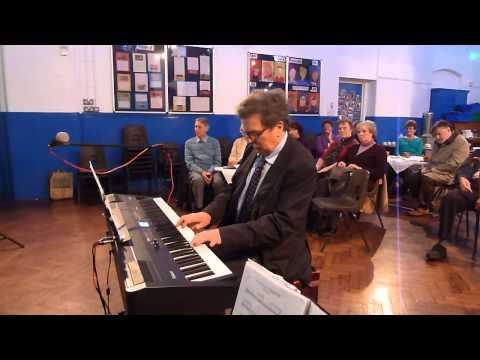 Howard Blake performing 'Walking in the Air' on piano at Downs Junior School, Brighton