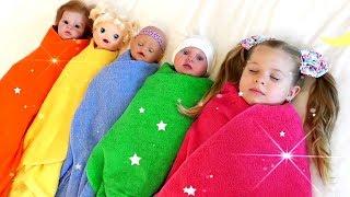 Diana pretend plays babysitting her dolls