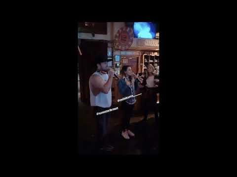 Mila Kunis and Scooter Braun singing karaoke and dancing at a party