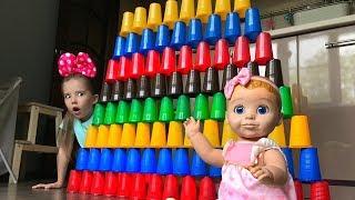 Маша играет в пирамиду. Кукла сломала стенку из стаканчиков