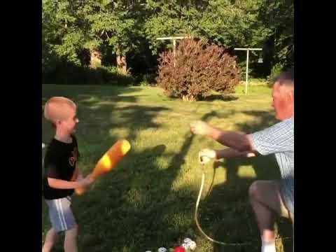 Kid and Grandpa Play Teeball Using Hose - 1056438