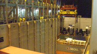 Oversized cargo on flatrack container is being discharged from container ship