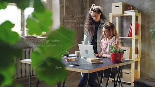 Young owners of small business are working with laptop in modern loft style office. Blonde is