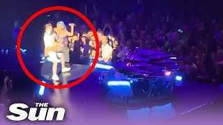 Lady Gaga falls off stage after fan drops her