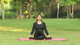A young girl practicing gomukhasana / the cow face yoga asana outside in a park