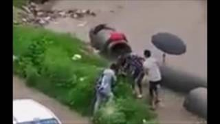person falls into an open drain while crossing flooded street in Nepal