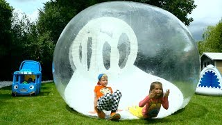Katy and Max playing with Giant clear ball playhouse for children