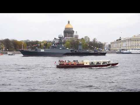 Boats on Neva sailing between Russian warships and submarines before 70th Victory Day