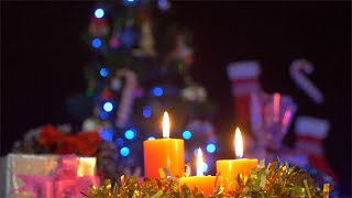 Beautiful burning candles with a decorated Christmas tree in the background