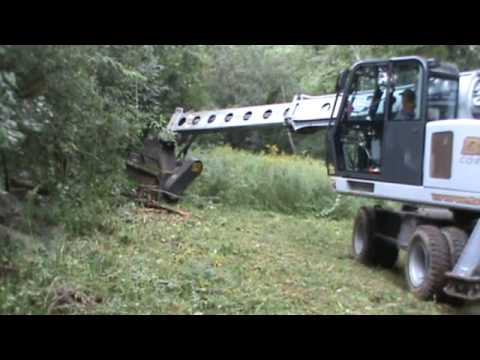 BMC clearing brush and small trees from sewer R O W  with rubber tire  Gradall excavator mower