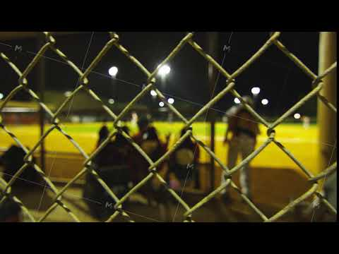 Shot of inside of dugout from behind fence during baseball game
