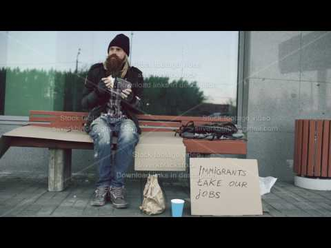 Homeless and jobless european man with cardboard sign eat sandwich on bench at city street because