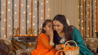 Happy mother and daughter laughing together while doing Diwali preparation - Festive background with lights