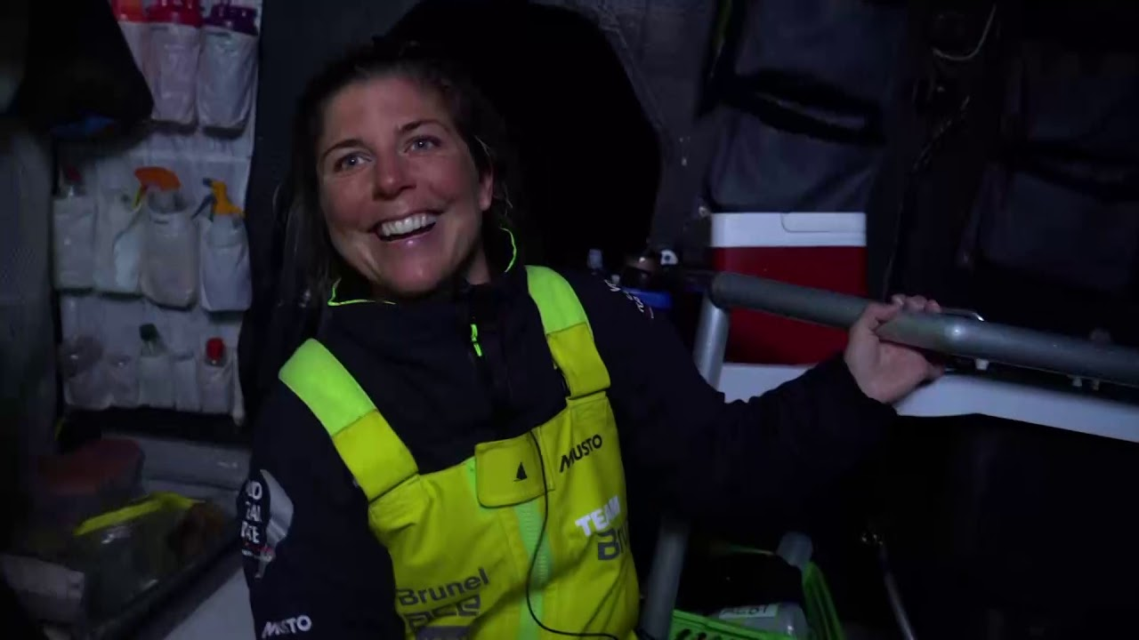 """Nina gets dressed below, then works the foredeck, the pit. Below, she talks about how she and Kyle haven't had much chance to rest, because they keep gybing in the off-watch. Thinks the next gybe will come during their off-watch. Stern cam footage of them surfing on starboard in big winds. We see a gybe in big winds. Nina, below: """"It's super windy and the swells quite big. I think I'm getting my first taste of what the Volvo Ocean Race is really like. It's pretty tough."""" Washing machine from the stern cam. Nina: """"Yeah, I did enjoy it. The waves are crazy, and the boys are just fearless when they're steering. And all you can do is just hold on with the mainsheet at the back of the boat; hold on for dear life. It's quite a ride. I'm enjoying it, but it's really hard."""" Slomo washing machine."""