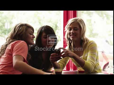 Medium Shot Young Woman Photographing Two Friends With Camera Phone In Cafe