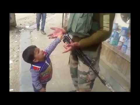 Kashmiri kid tries to snatch Indian cop's weapon (funny)
