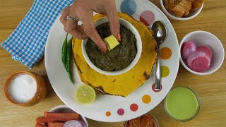 Closeup shot of woman hands adding butter to traditional Punjabi cuisine - Saag