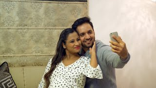The pregnant Indian couple happily taking selfies together using a smartphone