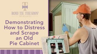 Demonstrating how to distress and scrape an old pie cabinet