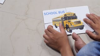 Closeup shot of a kid solving cardboard puzzle of a school bus