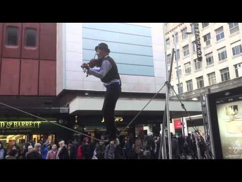Man Playing violin while walking on Tightrope in Manchester City Center