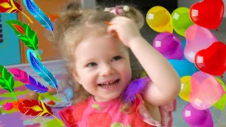 Mom and girls are popping balloons with surprises. Balloons with surprises by Sasha Kids Channel.